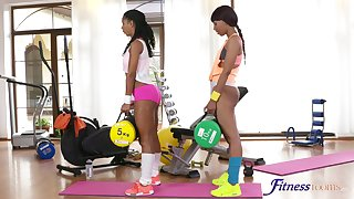 Ebony babes enjoy poking each other's dishevelled pussies on rub-down the gym floor